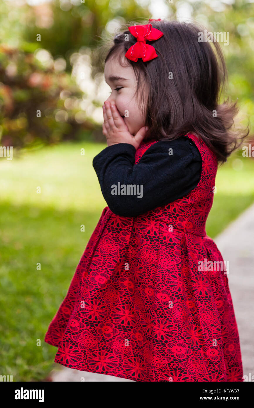 Shy, happy, smiling toddler baby girl giggling and laughing. Covering and hiding mouth and face to hide giggle, - Stock Image
