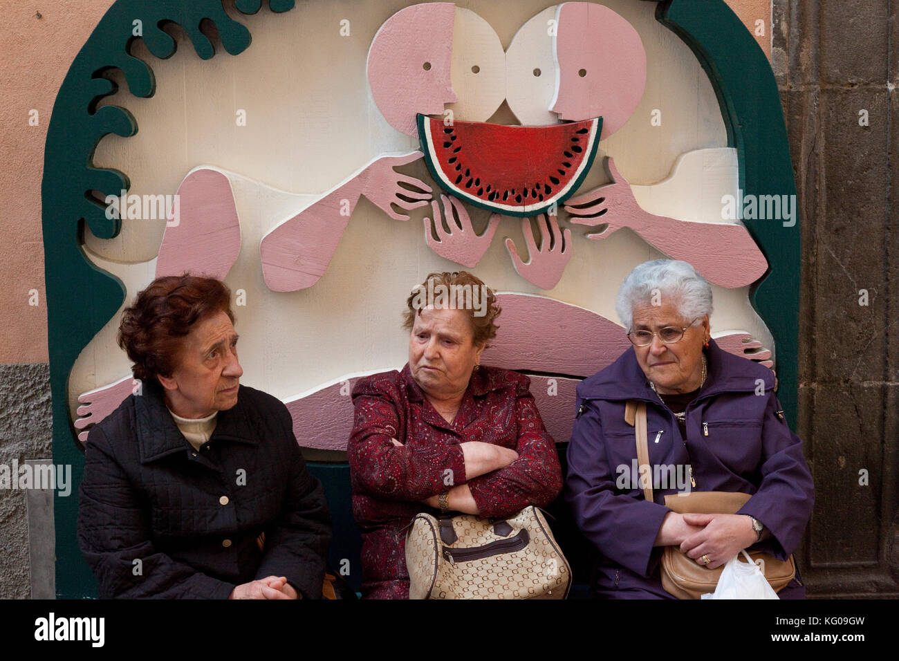 Elder residents of Orvieto, Italy pause to contemplate on a watermelon sculpture bench. - Stock Image