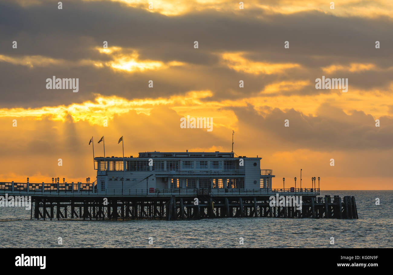 Sun rising with the suns rays shining through clouds on a cloudy morning at Worthing Pier in Worthing, West Sussex, - Stock Image