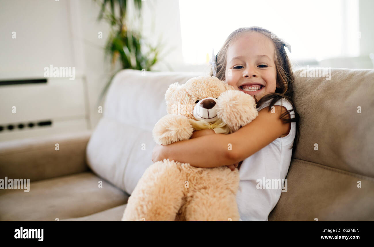 Cute little girl playing with teddy bear - Stock Image