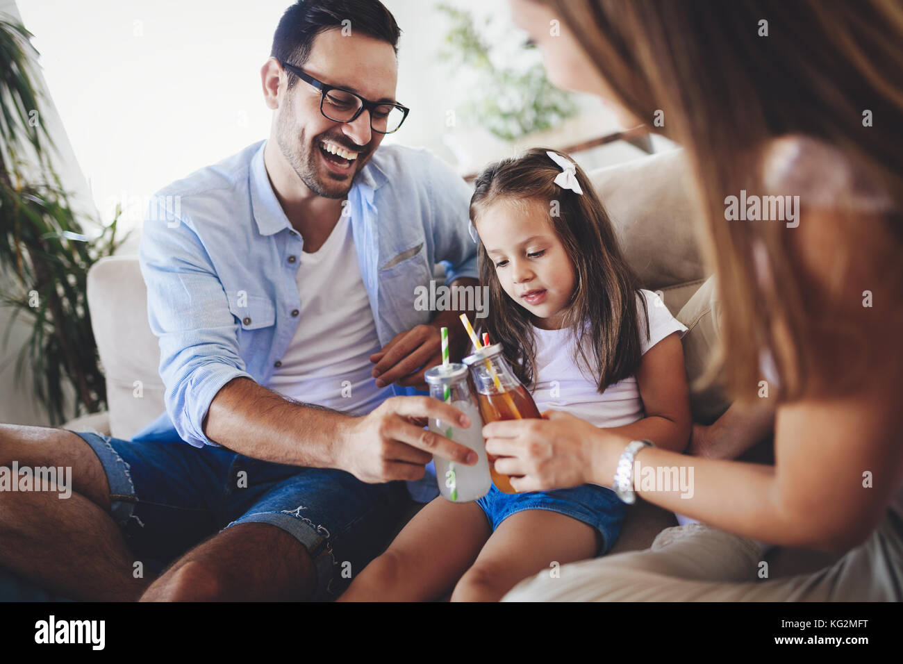 Happy family drinking juice together in their house - Stock Image