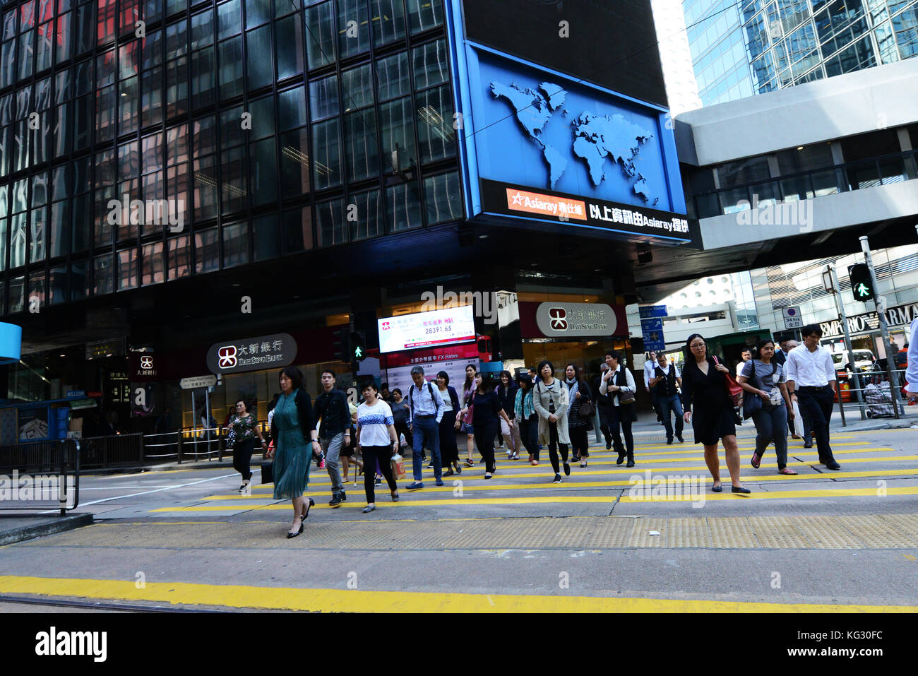 Pdestrians crossing Des Voeux Road in Central, Hong Kong. - Stock Image