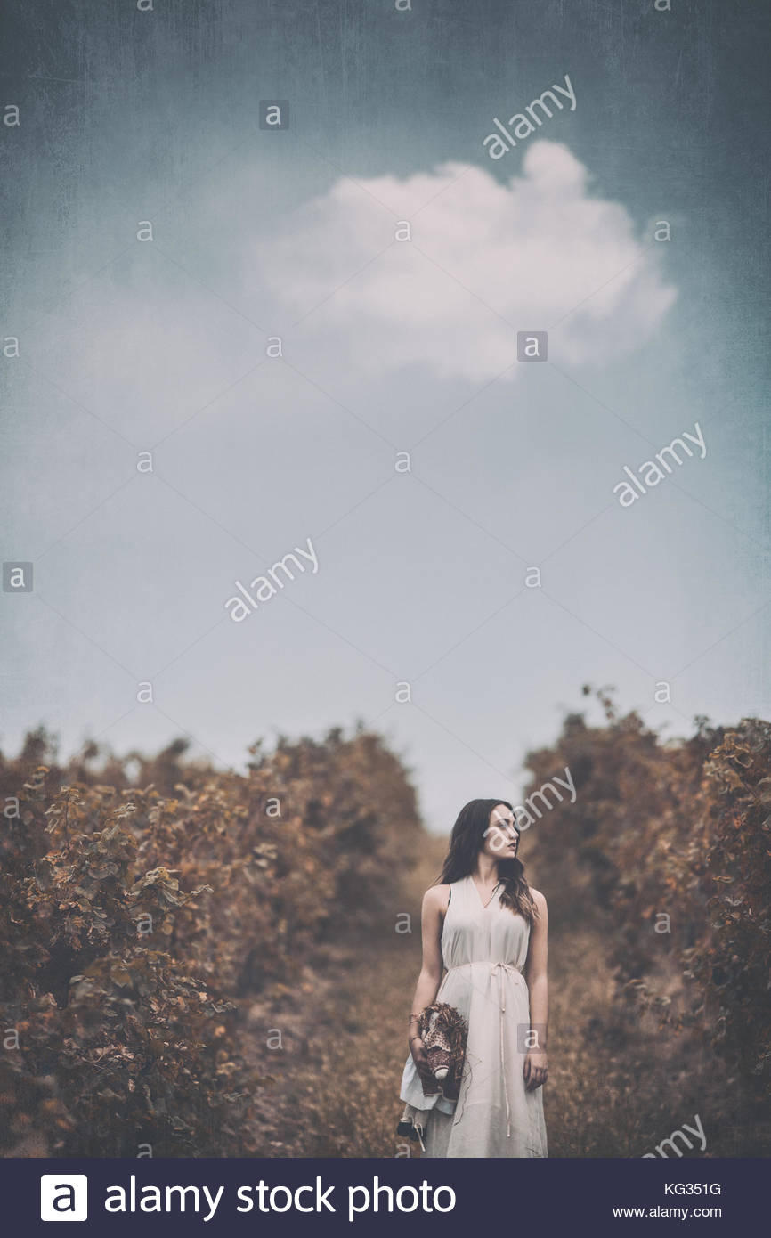 Girl Standing in a vineyard, in the countryside, lonely, blank look, holding a rag doll - Stock Image