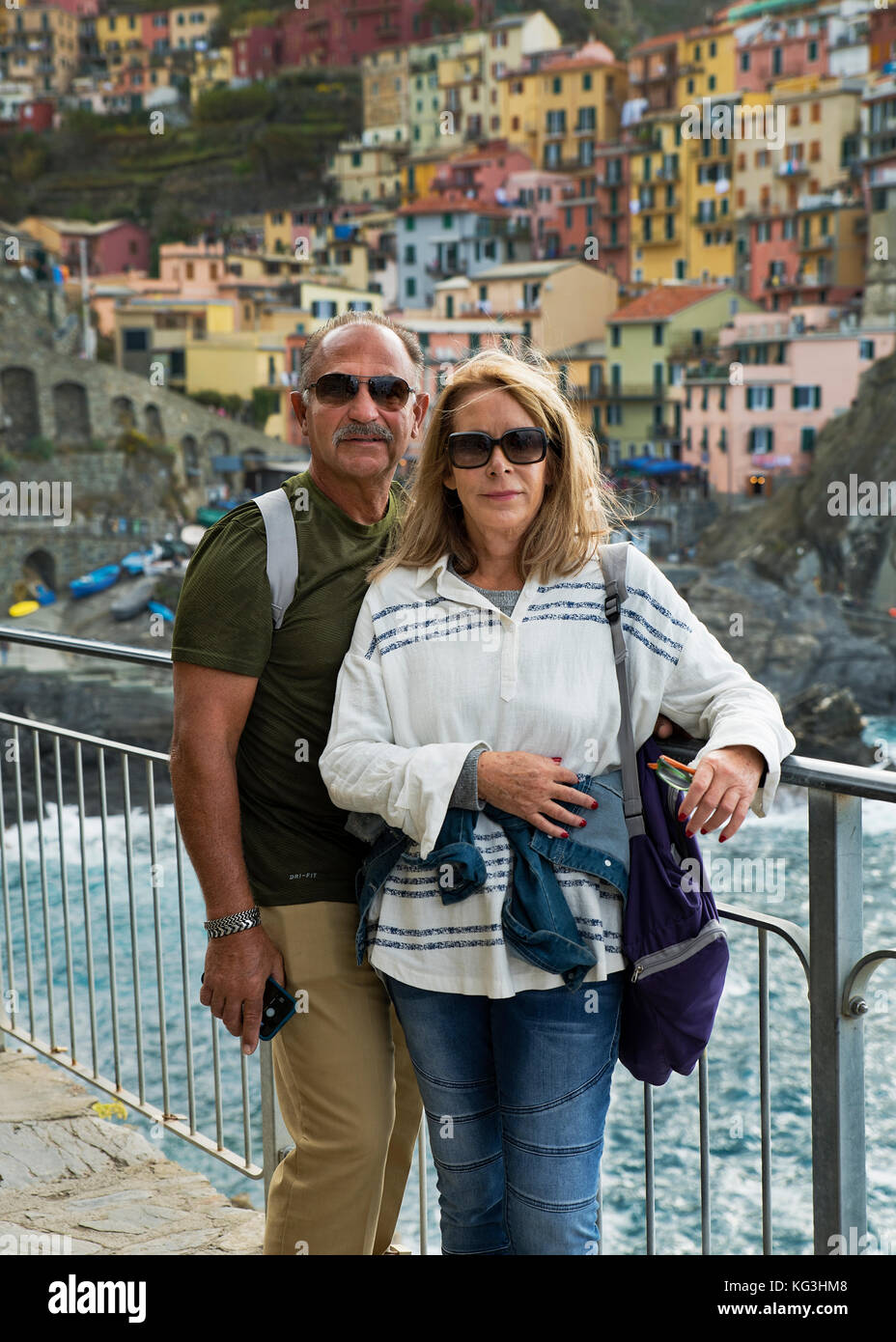Couple poses for a snapshot while traveling, in Riomaggiore, Cinque Terre, Italy. - Stock Image