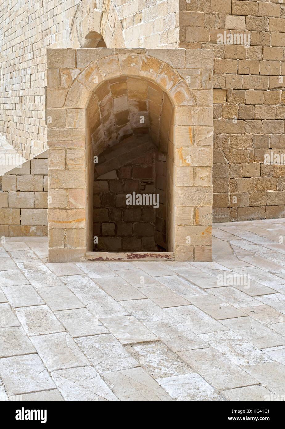 Ancient crypt entrance, bricks stone wall and tiled stone floor beside Kayet bay castle, Alexandria, Egypt - Stock Image