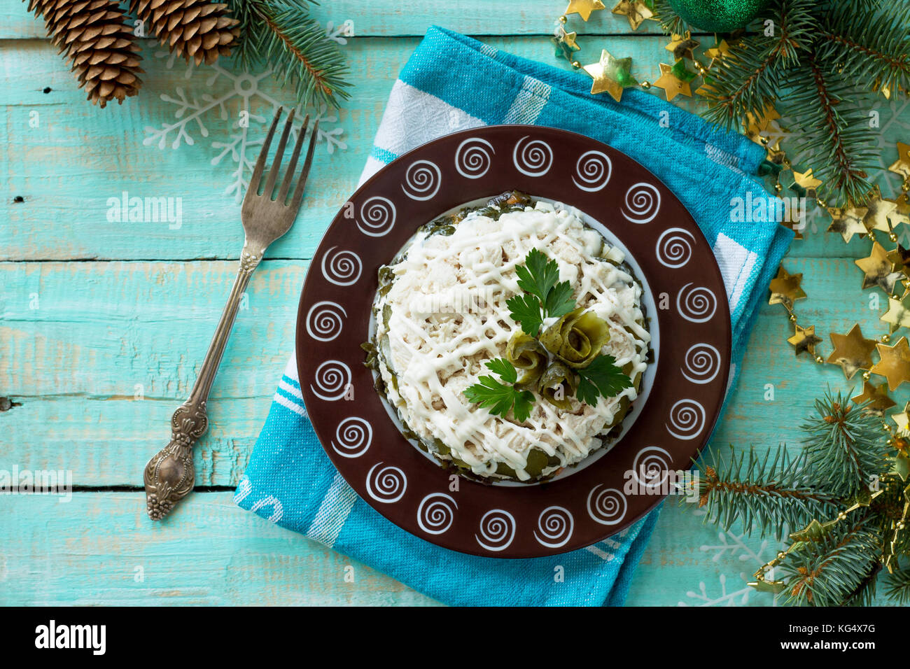 Home snack on the kitchen wooden table. Salad with chicken, rice and sea cabbage. - Stock Image