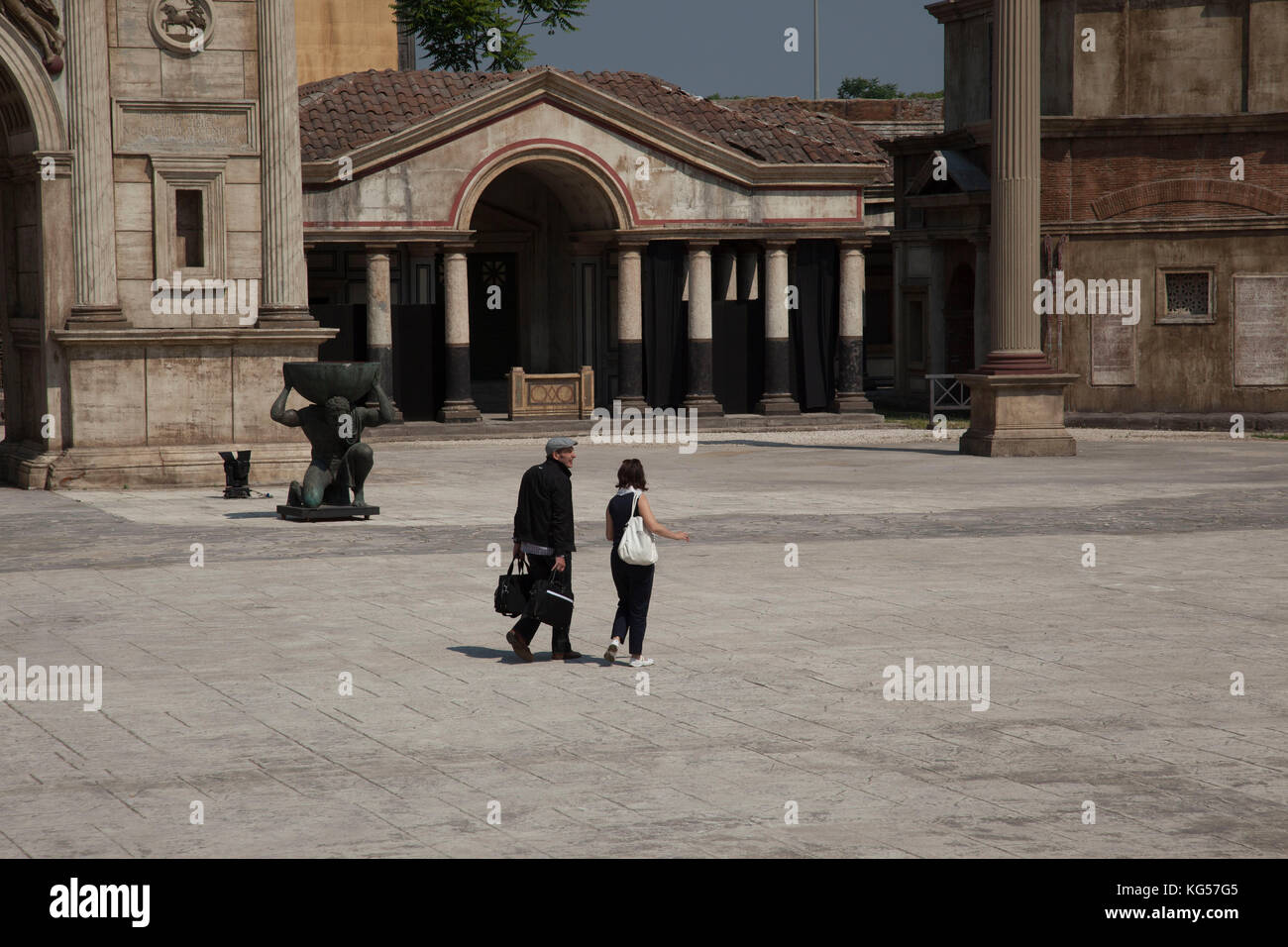 A man and a woman walk across the Roman set at the Cinecittà film studios in Rome, Italy. - Stock Image