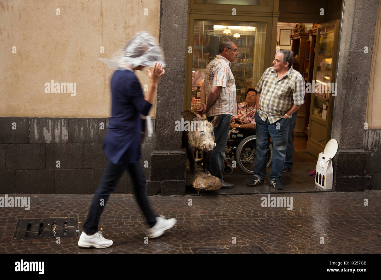 A woman covers her head in plastic as she walks past a butcher shop in the rain in the Umbrian town of Orvieto, - Stock Image