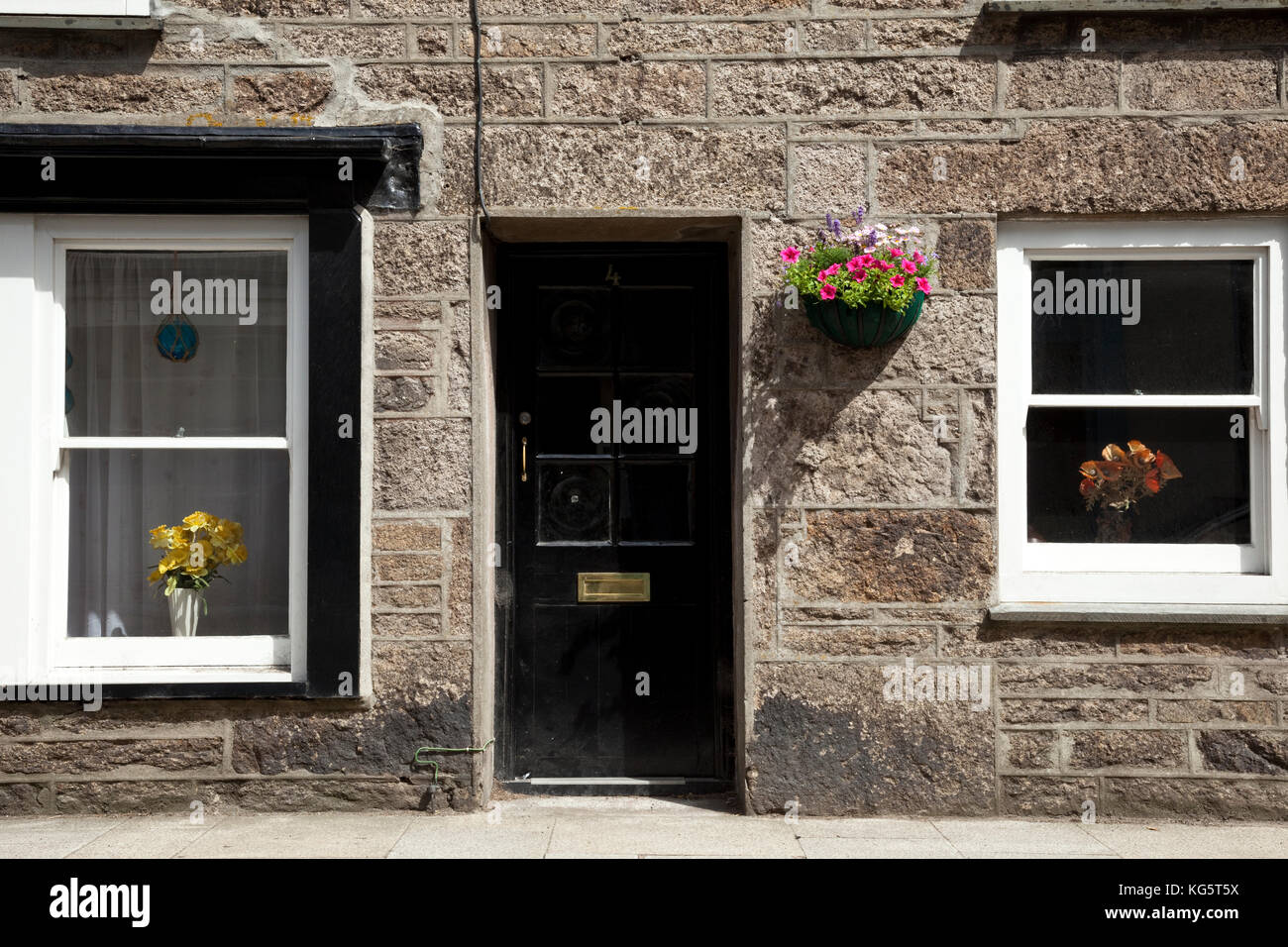 Flowers adorn the windows and wall of a home in Saint Just, Cornwall, England - Stock Image