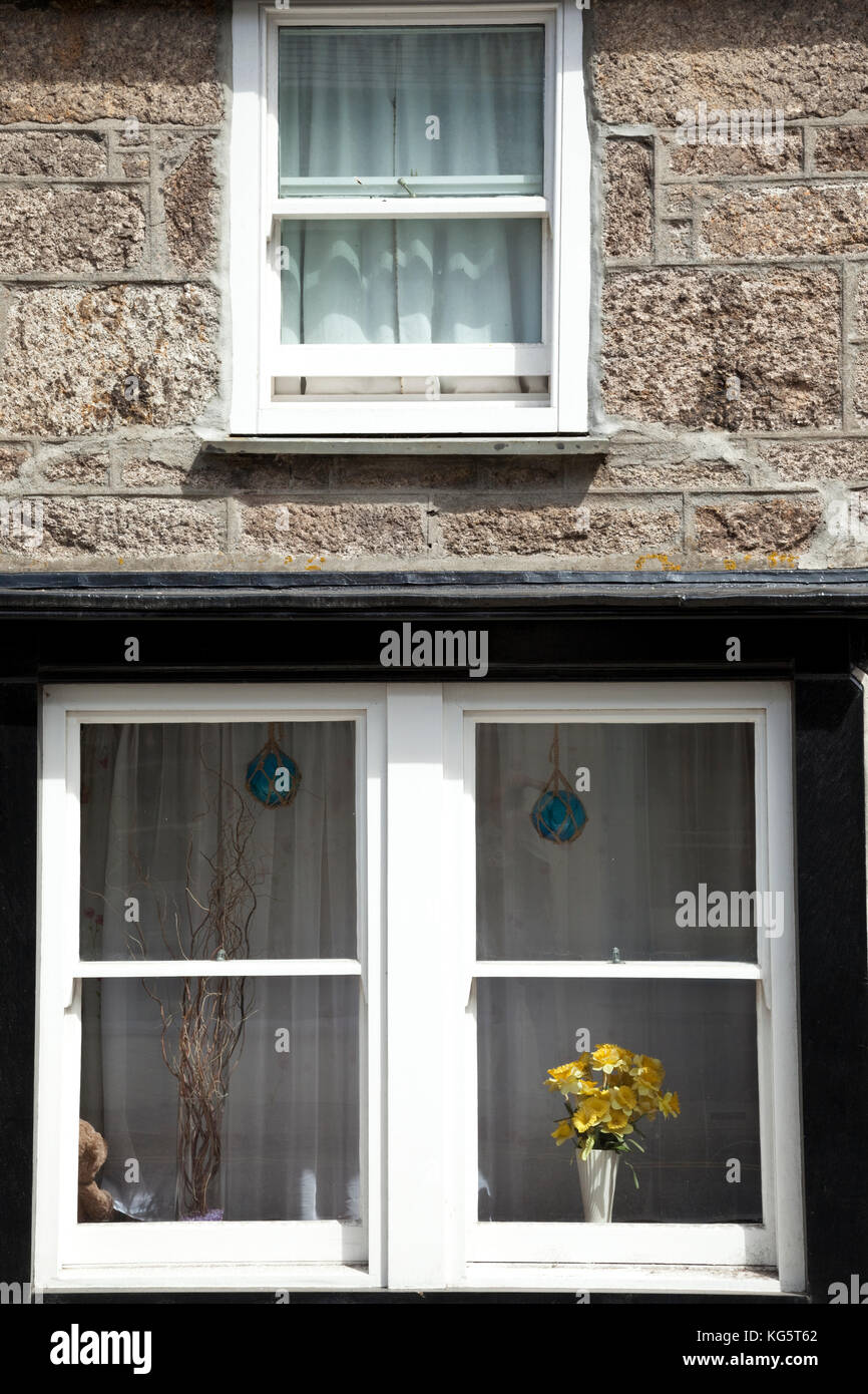 Yellow flowers adorn a window in Saint Just, Cornwall, England. - Stock Image