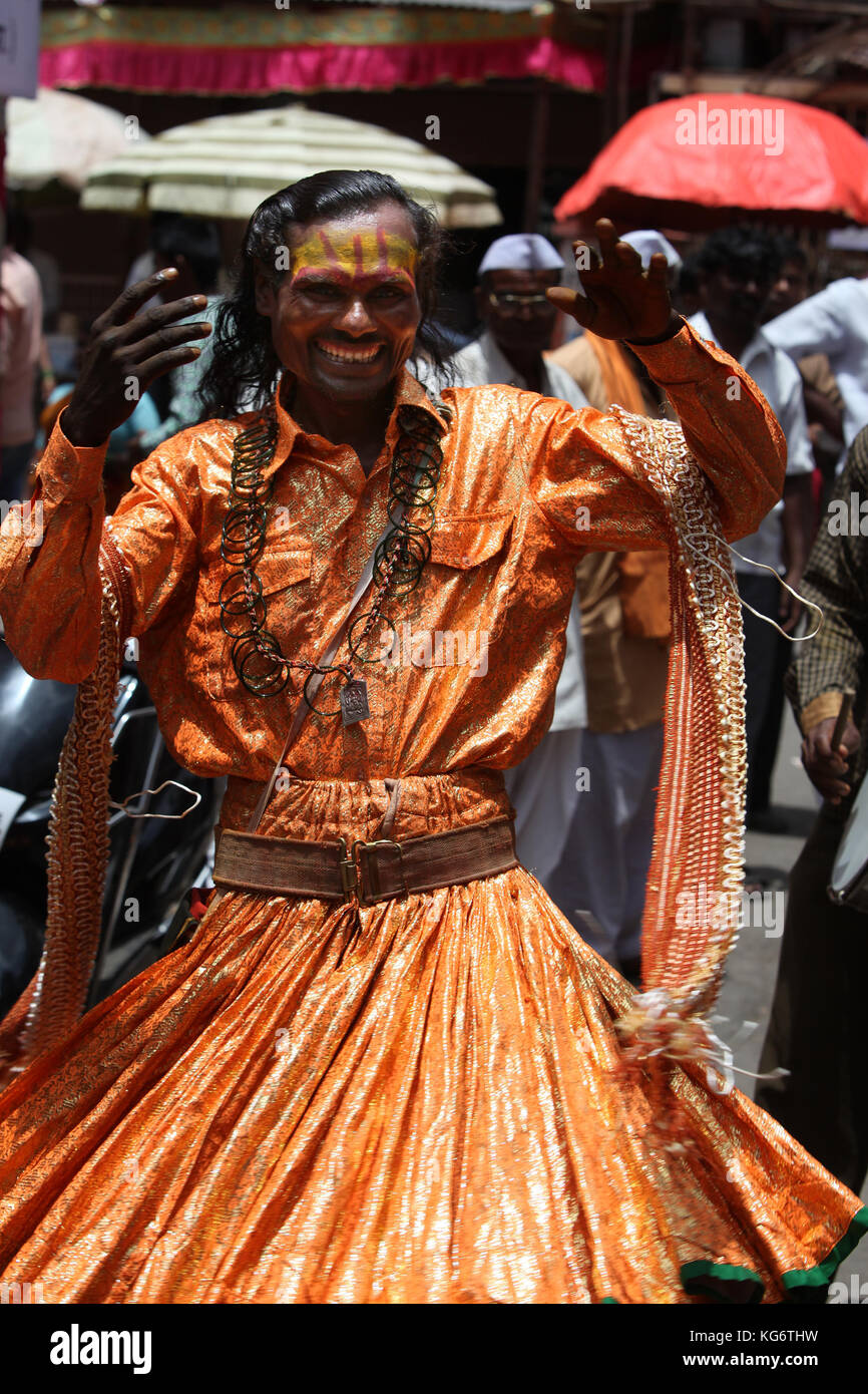 A man dressed in a traditional dancing attire during a religious festival in India. - Stock Image