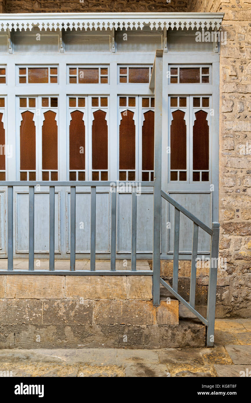 Array of wooden blue doors with yellow glass over stone wall, wooden blue balustrade, and stone stairs at historical - Stock Image