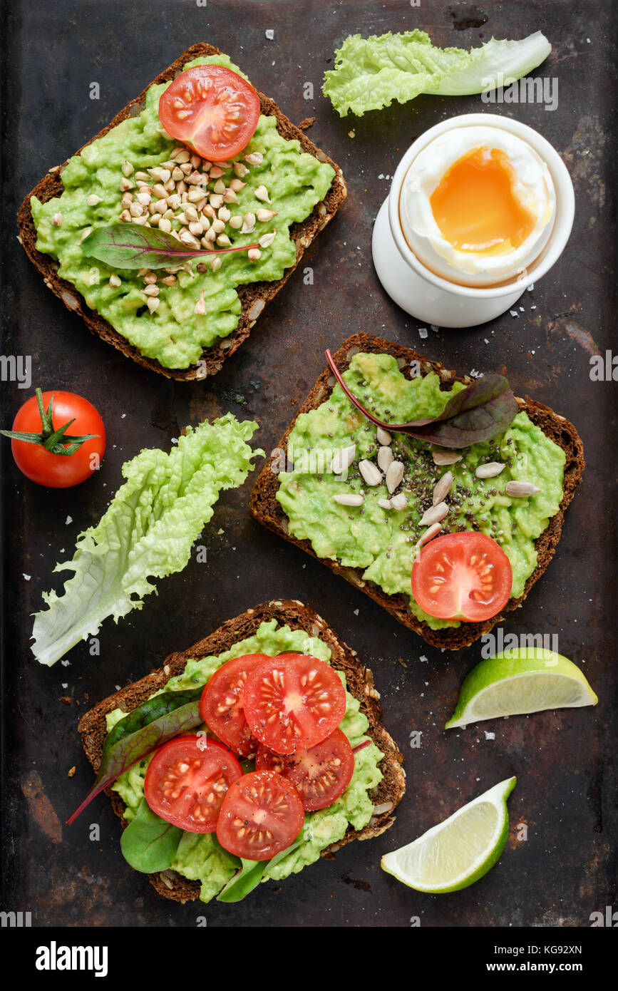 Healthy green veggie toast with avocado, tomato, sprouts and seeds and boiled egg on rusty background. Table top - Stock Image