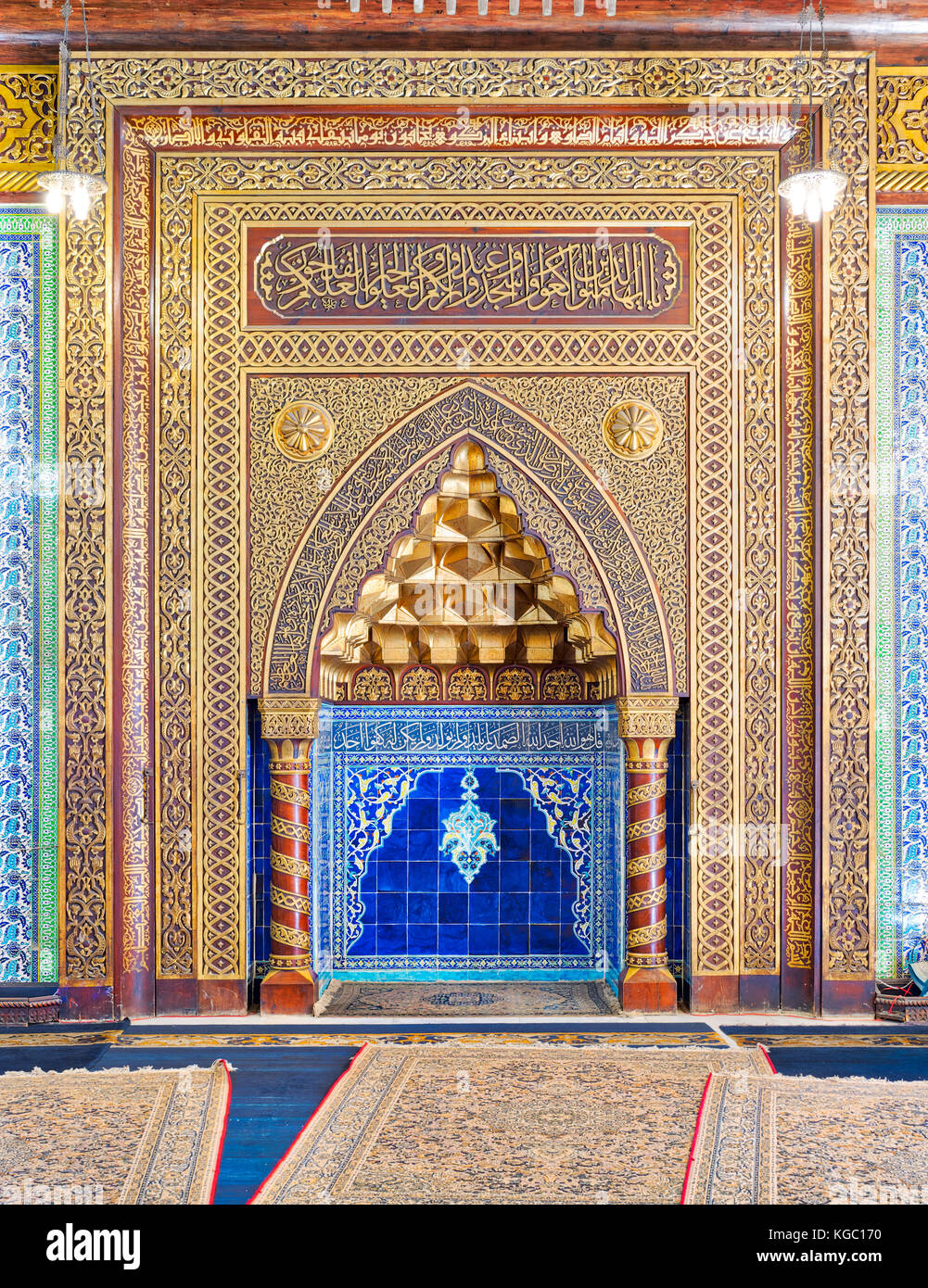 Golden ornate arched mihrab (niche) with floral pattern, blue Turkish ceramic tiles and arabic calligraphy at the - Stock Image