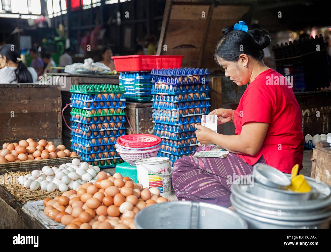 Burmese woman selling eggs and counting money at food market in Yangon / Rangoon, Myanmar / Burma - Stock Image