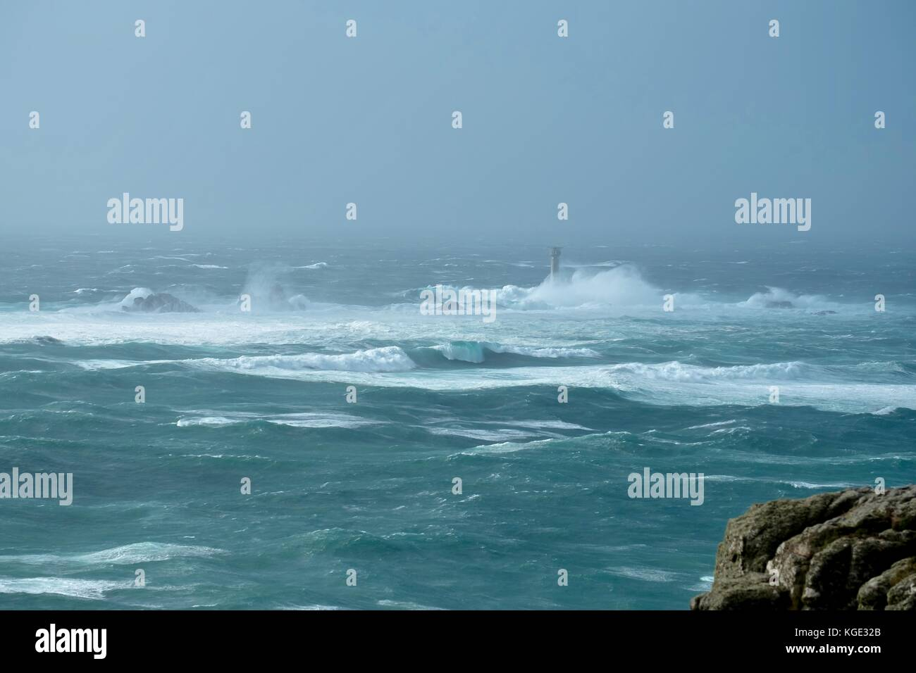 A storm hitting Lands End in Cornwall with waves smashing into the 35 metre tall Longships lighthouse. - Stock Image