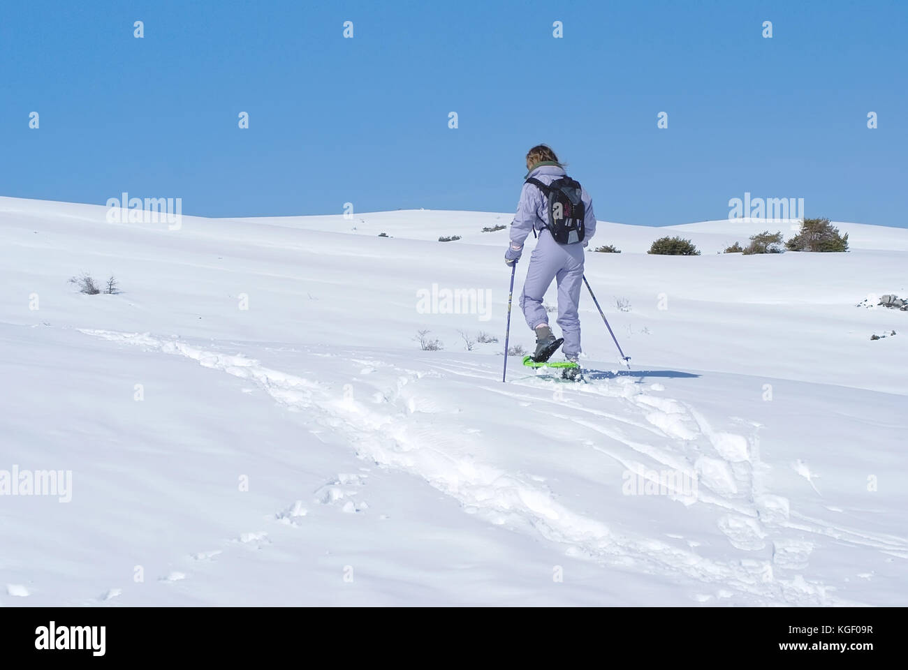 woman-climbing-a-moutain-with-snowshoes-