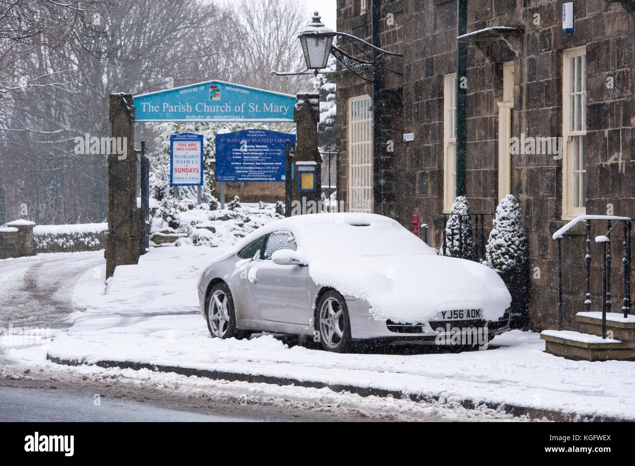 Cold, snowy winter day with snow-covered car parked outside stone cottages & church gate in village - Burley - Stock Image