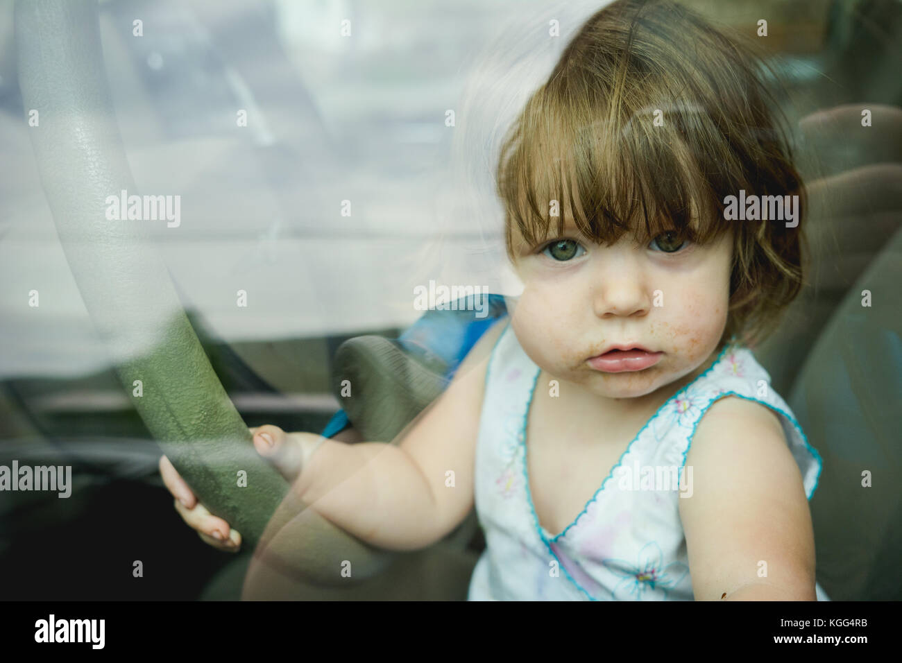Child looking out of a car window, holding on to steering wheel - Stock Image