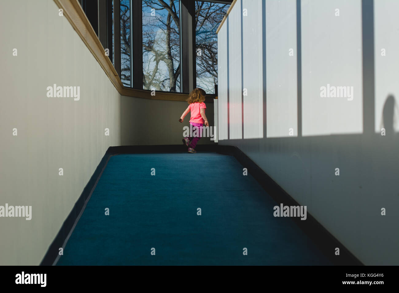 A toddler walks down a well lit hallway. - Stock Image