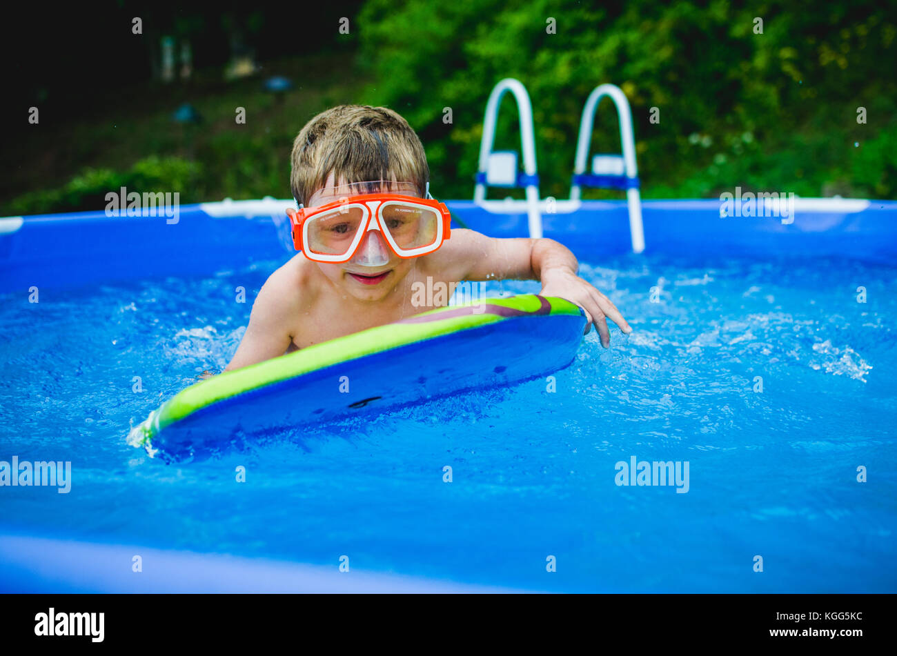 8-9 year old playing on a boogie board in a pool in summer. - Stock Image