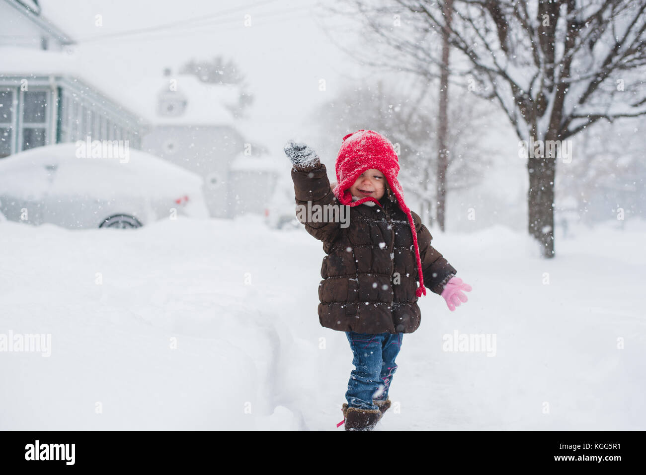 2-3 year old standing in the middle of a snow storm. - Stock Image