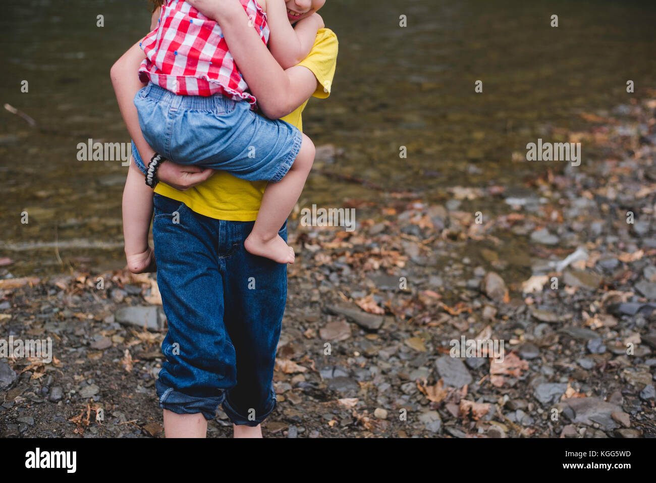 A boy carries a child in his arms - Stock Image