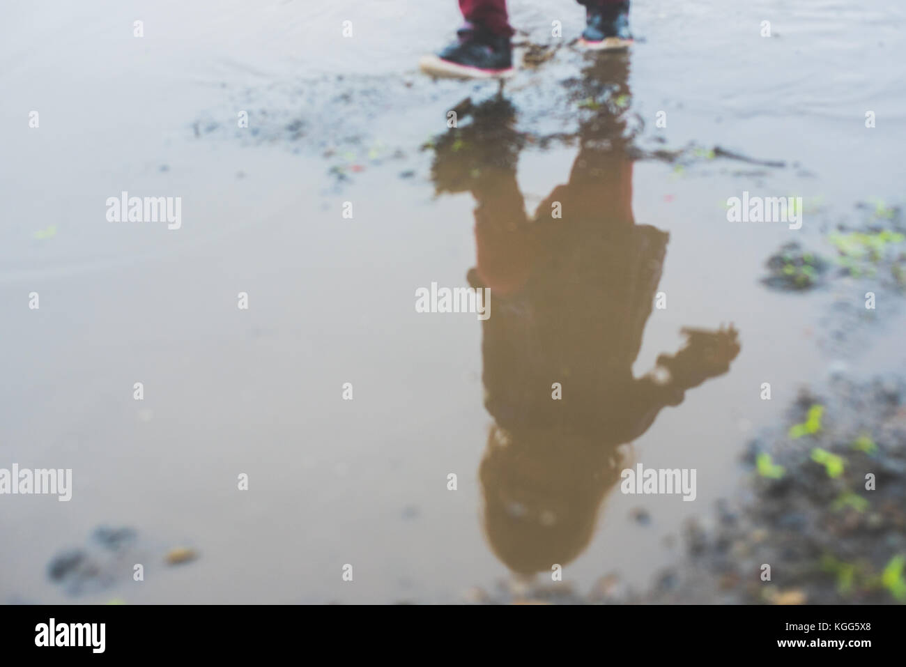 Child walking in a mud puddle - Stock Image