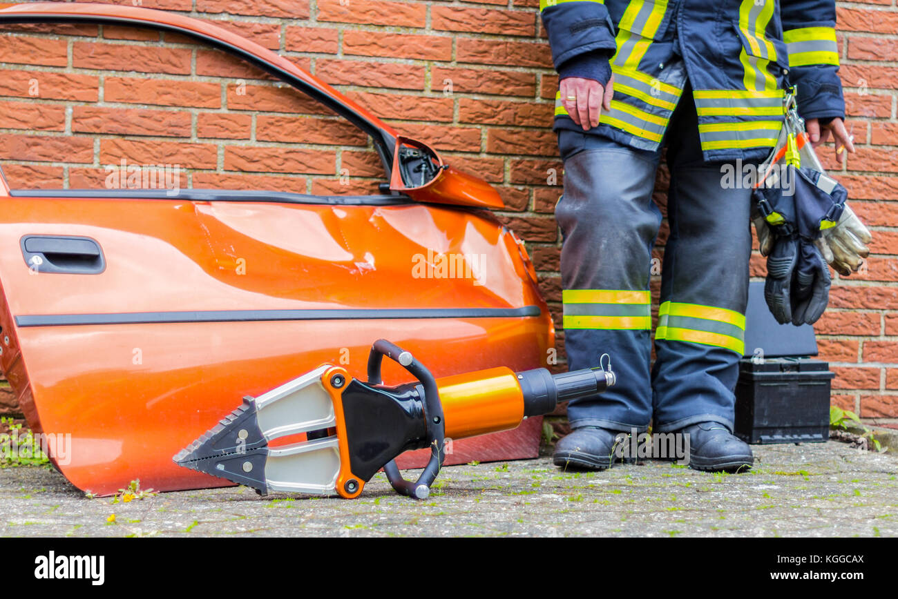 german firefighter stands near a car door with an emergency tool - Stock Image