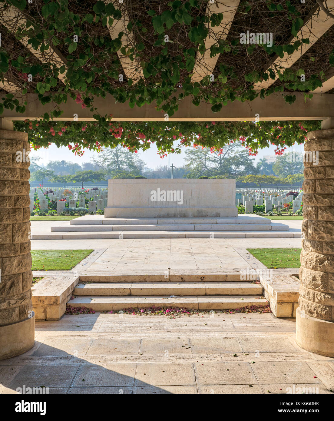 Entrance of Heliopolis Commonwealth War Cemetery with two stone bricks columns and climber green plants, Cairo, - Stock Image