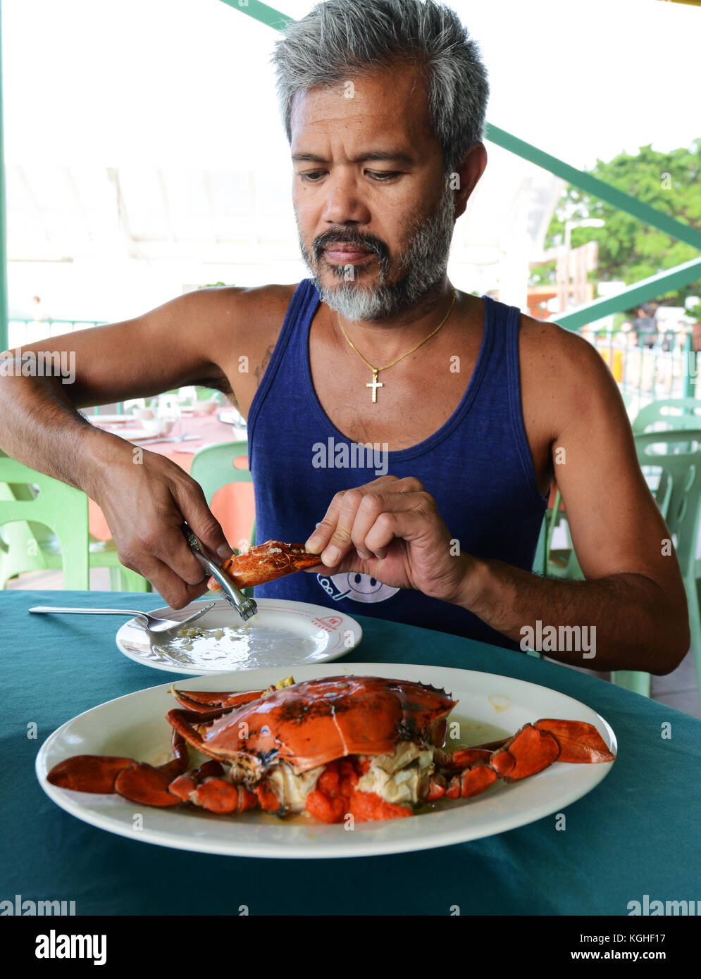 A tourist enjoying a female crab with her eggs. - Stock Image