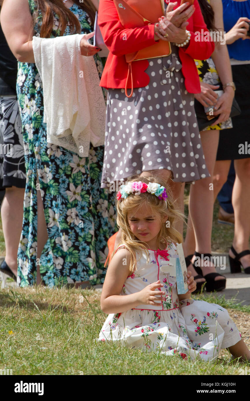 Pretty small girl in a floral headband at a wedding - Stock Image