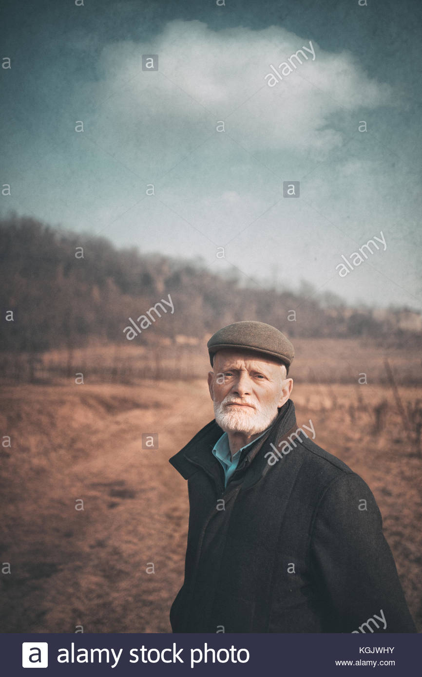 Old man standing in a field in the countryside - Stock Image
