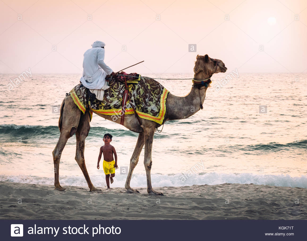 boy-stares-up-in-amazement-at-arabic-man-wearing-a-traditional-thawb-KGK71T.jpg