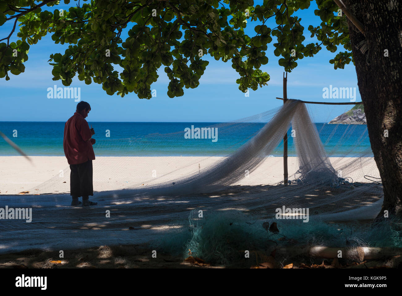 Caiçara fisherman fixing a fishing net at Bonete Beach, Ilhabela, Brazil - Stock Image
