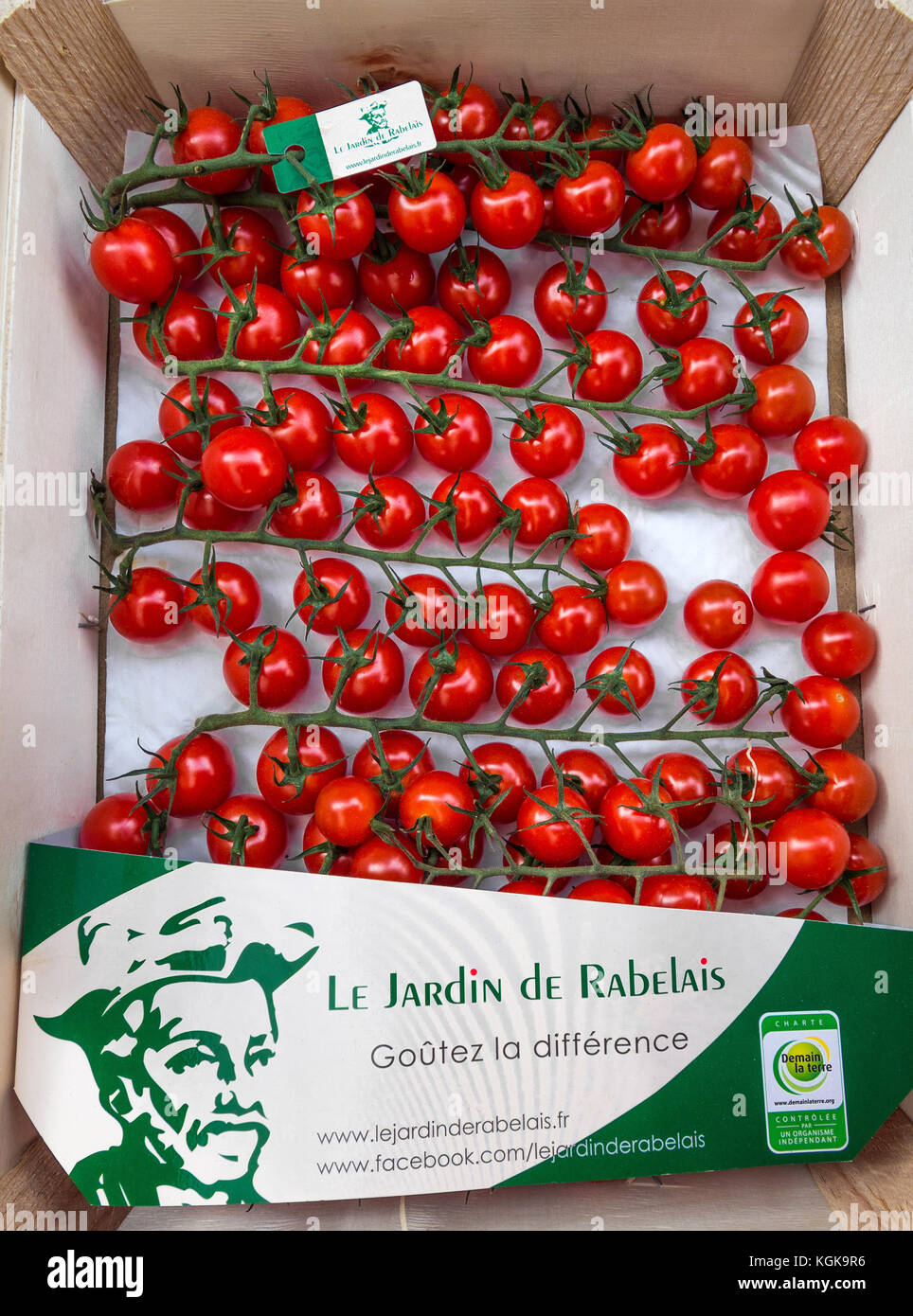 Box of cherry tomatoes on French market stall. - Stock Image