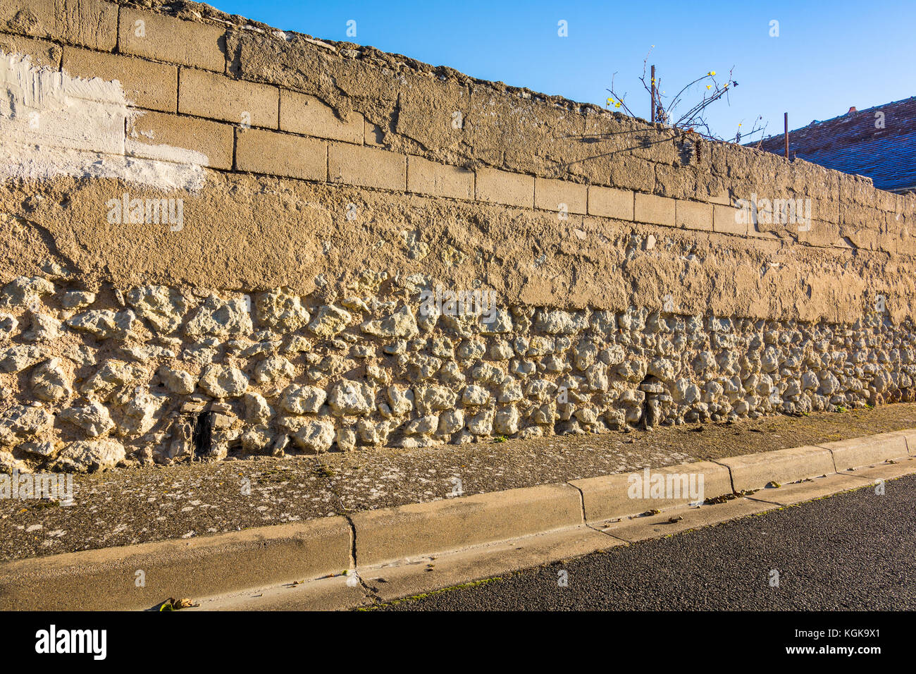 Old stone and breeze block wall in need of rendering - France. - Stock Image