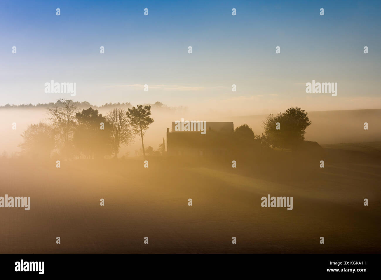 Silhouette of farmhouse in misty landscape at dawn - France. - Stock Image