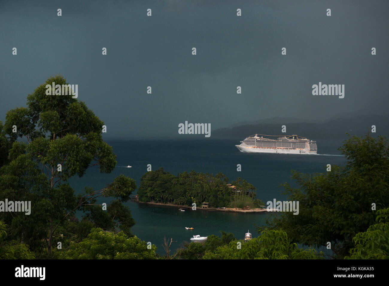 Cruise ship facing an approaching storm at Canal de São Sebastião, Ilhabela, Brazil - Stock Image