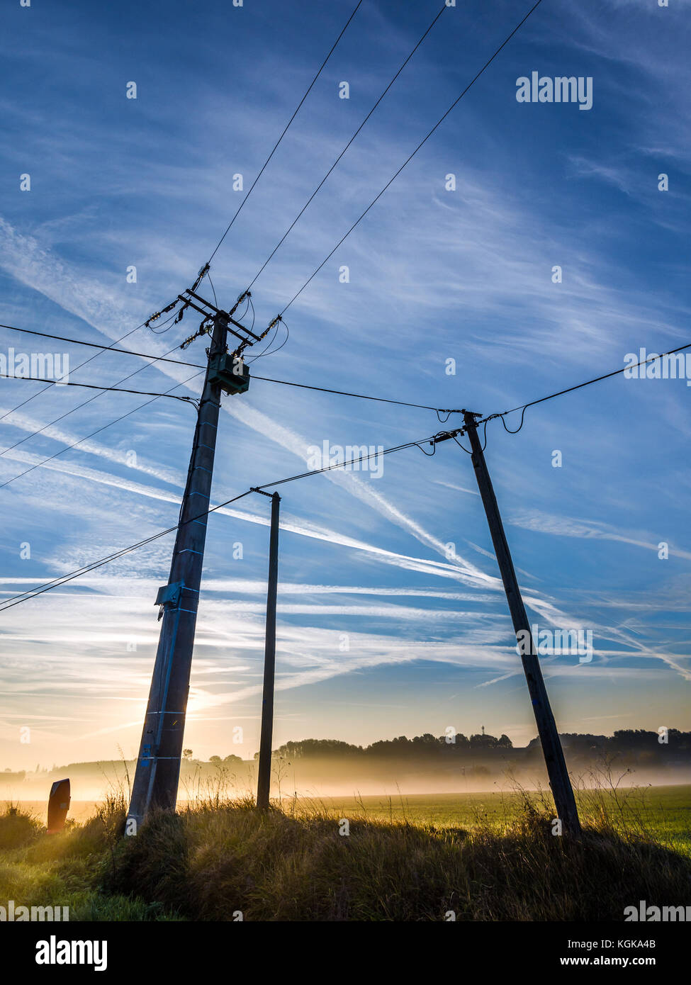 Electricity power lines and aircraft contrails - France. - Stock Image
