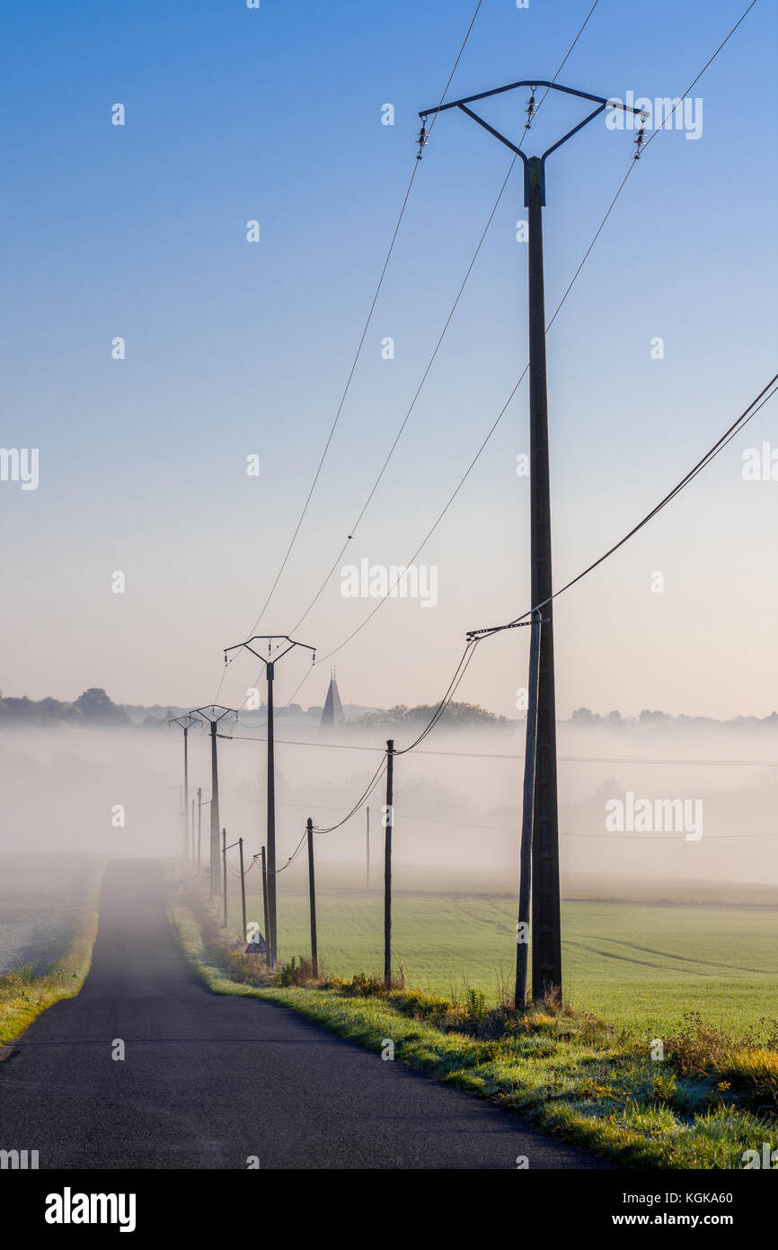 Electricity power lines alongside country road - France. - Stock Image