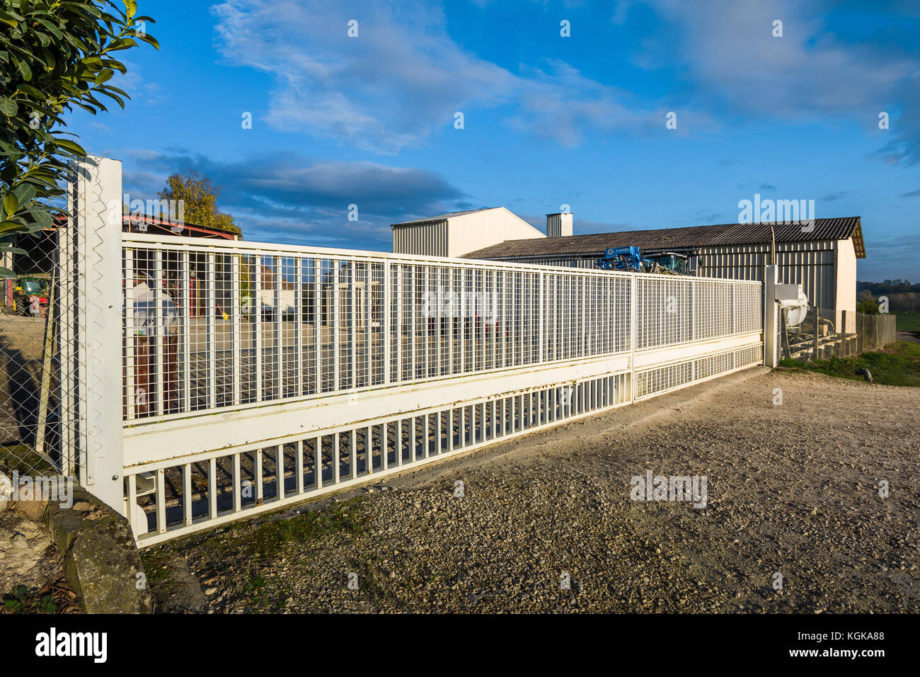 Long, sliding metal farm gate - France. - Stock Image