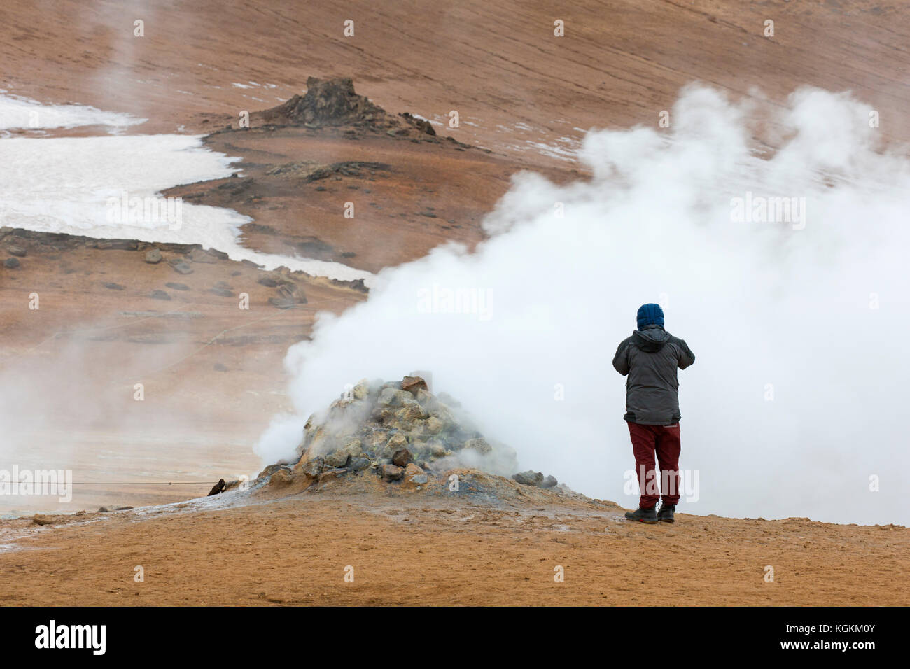 Tourist photographing steaming fumarole at Hverir, geothermal area near Námafjall, Norðurland eystra / - Stock Image