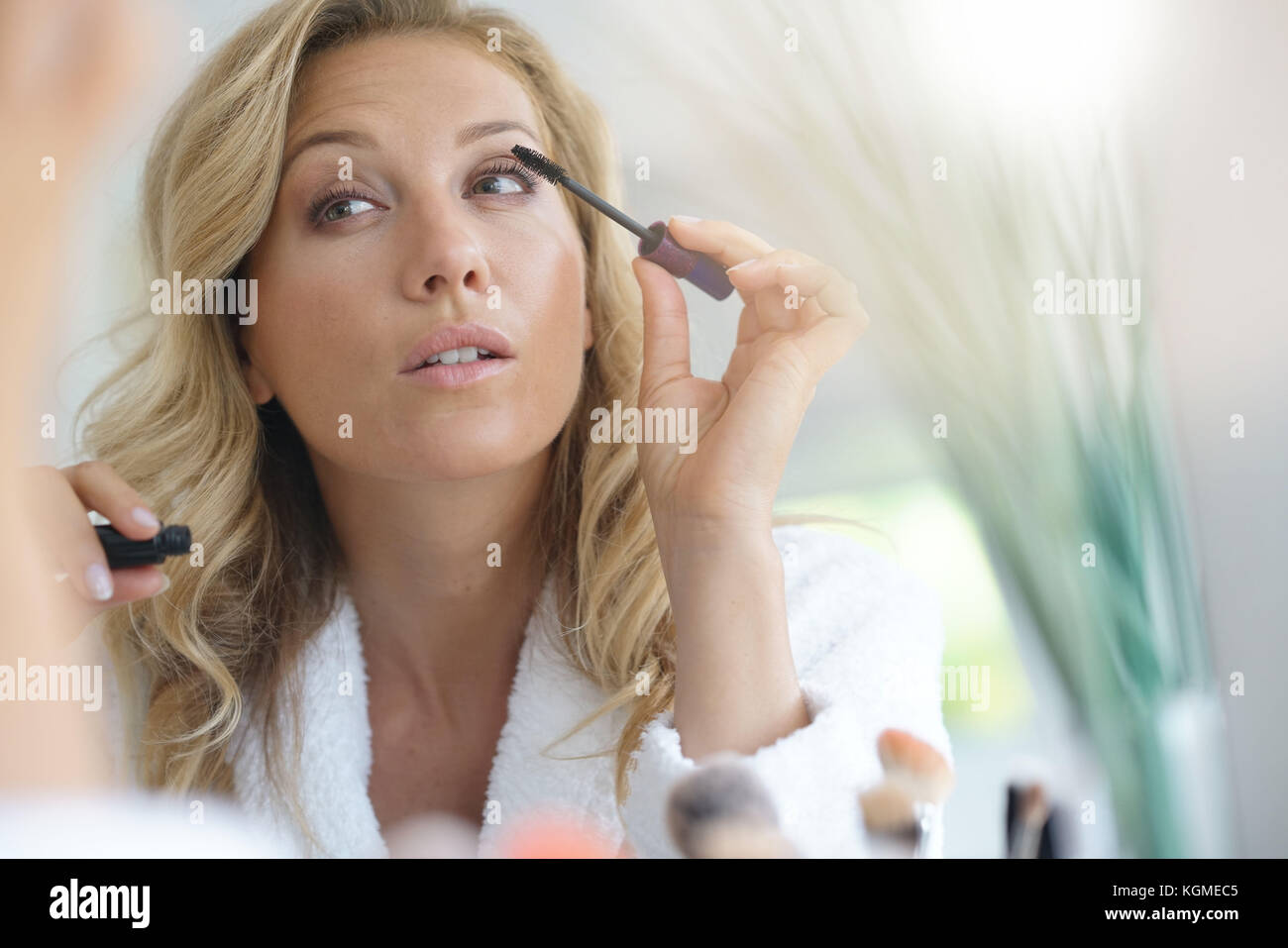 Portrait of beautiful blond woman applying mascara in front of mirror - Stock Image