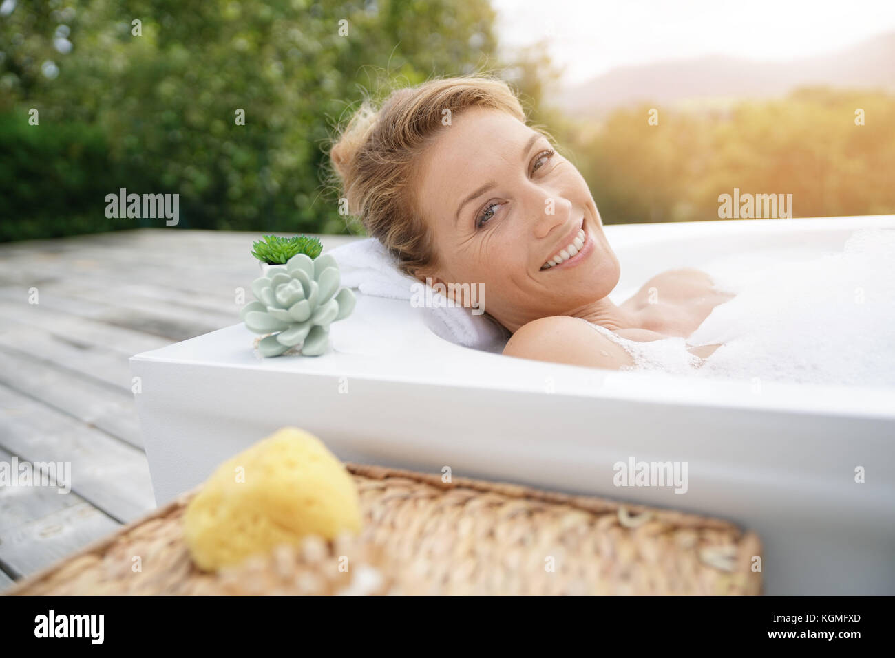 Beautiful woman relaxing in outdoor bathtub - Stock Image