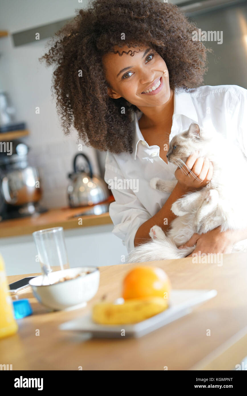 Mixed-race woman in kitchen cuddling cat - Stock Image