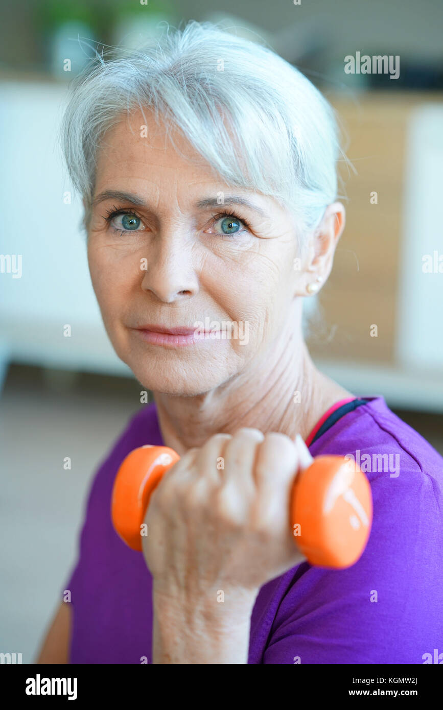 Portrait of senior woman lifting dumbbells - Stock Image