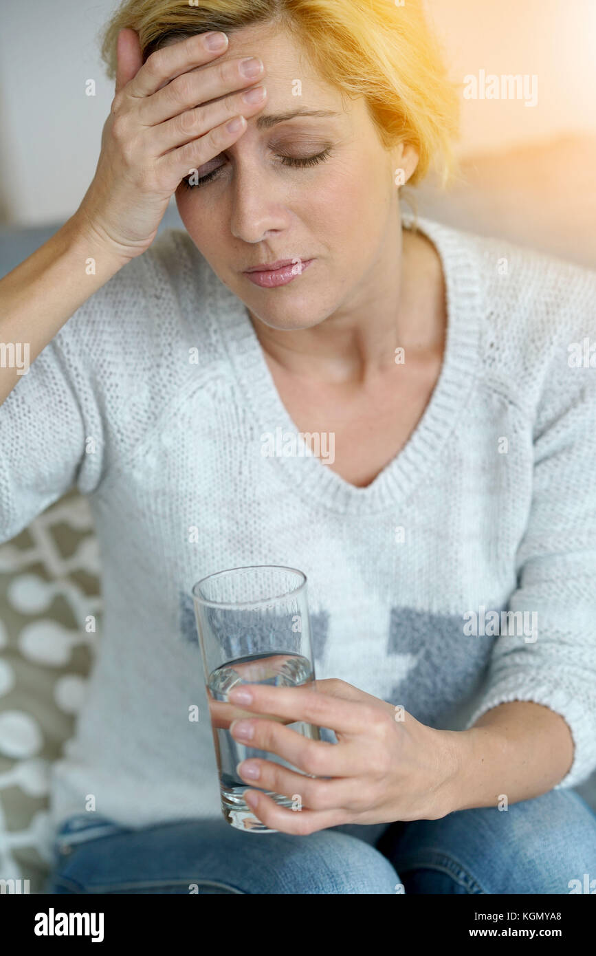Middle-aged woman at home taking pill to ease headache - Stock Image