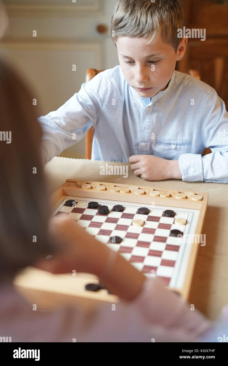 Kids playing checkers at home - Stock Image