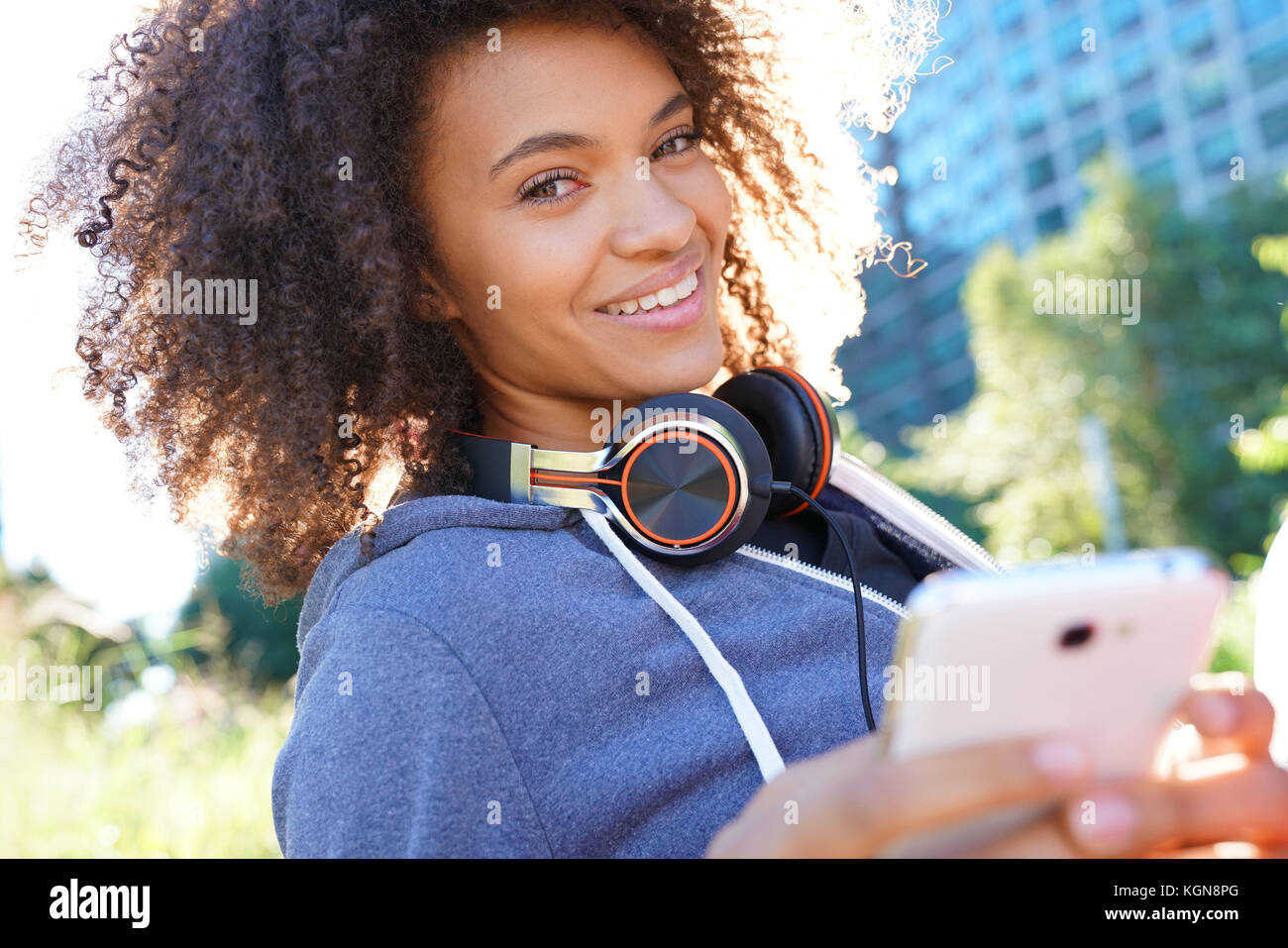 Portrait of mixed race girl in park listening to music on smartphone - Stock Image
